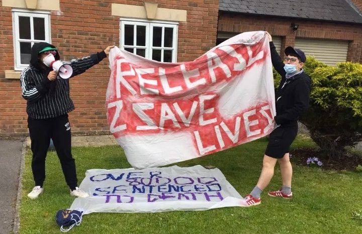 Picture shows two people holding a banner saying 'release 2 save lives'