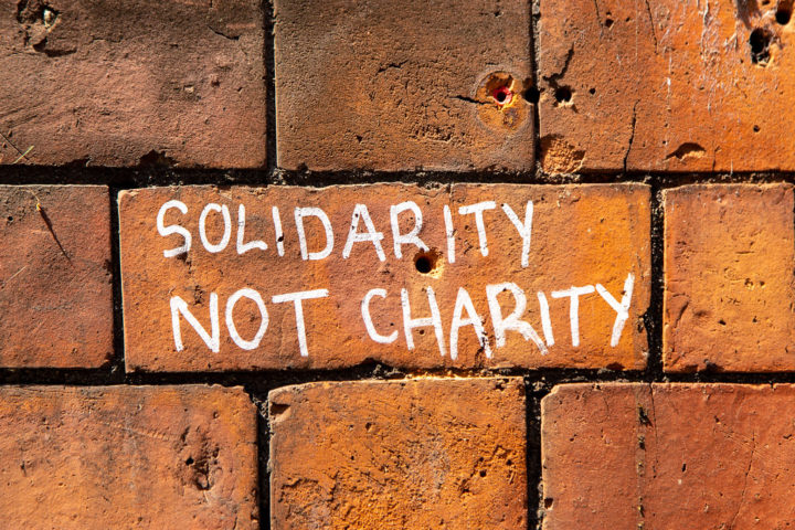 Image shows solidarity not charity sprayed on a brick wall