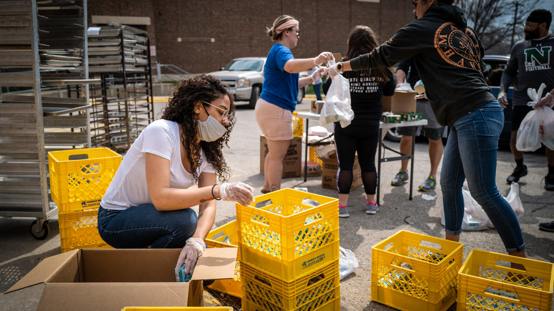 Image shows a group of people packing supplies into yellow crates