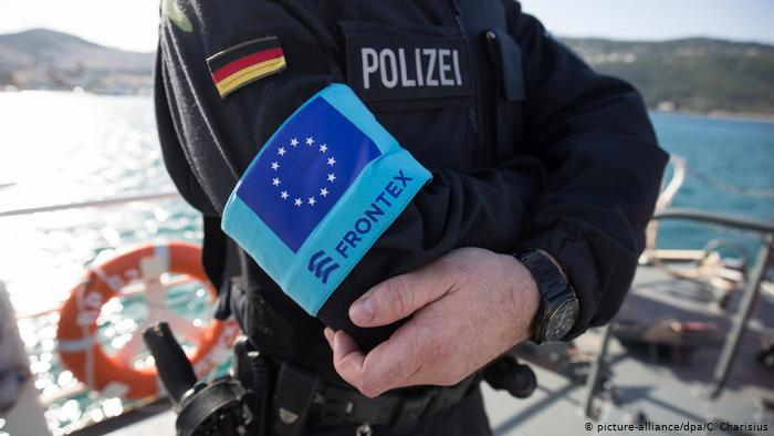Image shows a picture of a FRONTEX border guard with their arms crossed