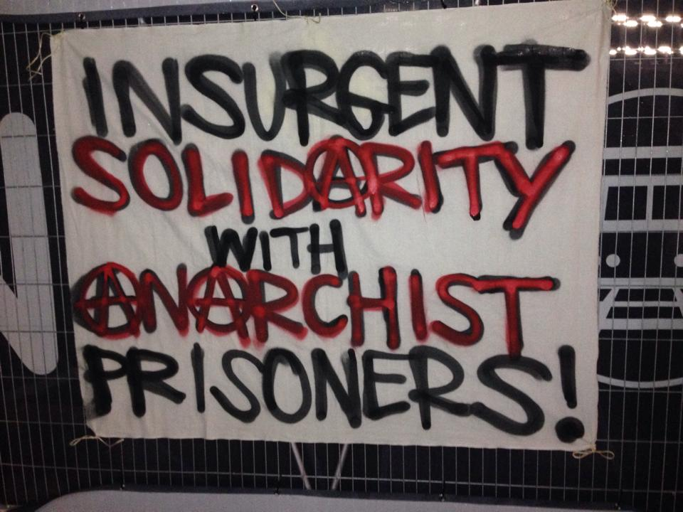 Image is a banner saying insurgent solidarity with anarchist prisoners