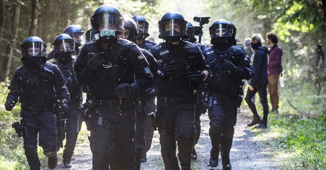 Image shows a group of police running in a forest