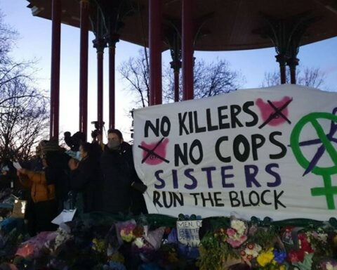 Image shows a banner saying 'No Killers, No cops. Sisters run the block""