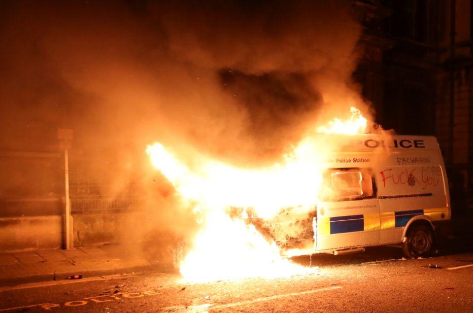 Image shows a police riot van burning