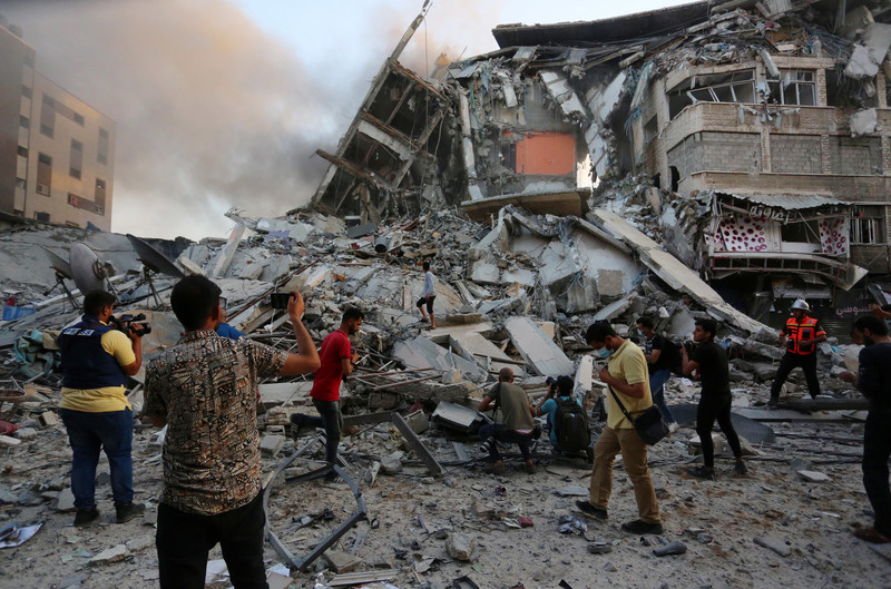 Palestinians inspect the rubble of al-Shurouk tower after it was hit by an Israeli airstrike on 12 May. Ashraf Amra APA images)