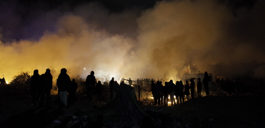 Image shows a group of people on a mound with a fire